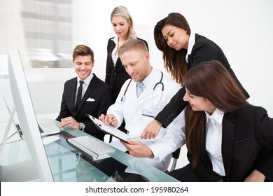 Male doctor and businesspeople discussing over clipboard at desk in office