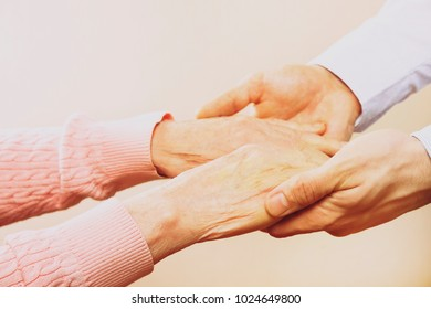 Male doctor care giver holding hands of elderly pensioner woman patient, reassuring in nursing home. Adult man, son carefully helping old mother to get up. Background, close up, copy space, overhead.