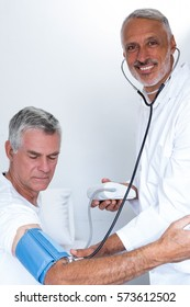 Male doctor checking senior mans blood pressure in hospital