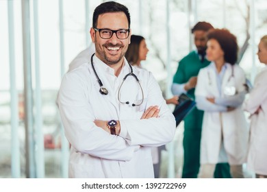 Male doctor with colleagues in background, doctor looking at camera with emergency team in background