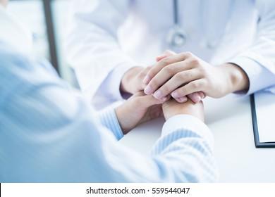 männlicher Arzt, der den Patienten im Beratungsraum tröstet