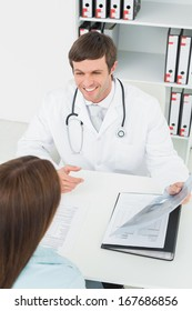Male doctor in conversation with female patient at desk in medical office