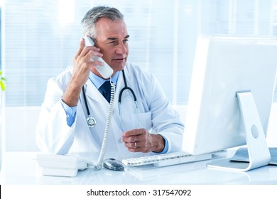 Male doctor in conversation through telephone while looking at computer in hospital