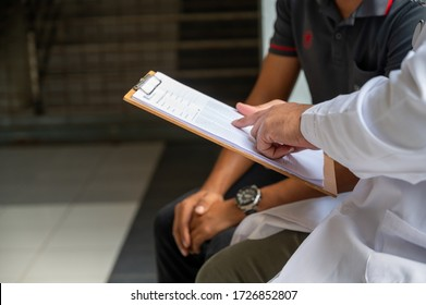 The male doctor is diagnosing the disease with a document in his hand