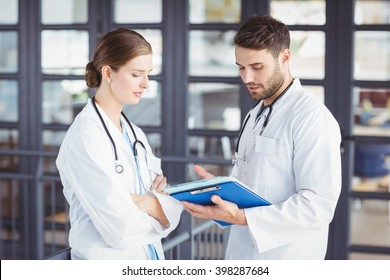 Male doctor discussing with female colleague at hospital