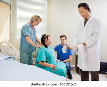 Male doctor examining ctg report with birthing mother, husband and nurse