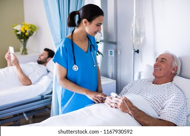 Male doctor examining female senior patient in the ward at hospital