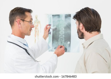 Male doctor explaining spine x-ray to patient in the medical office