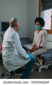 Male doctor with face mask examining his female patient in clinic office
