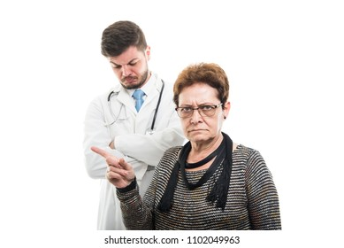 Male doctor and female senior patient showing denial gesture looking sad isolated on white background