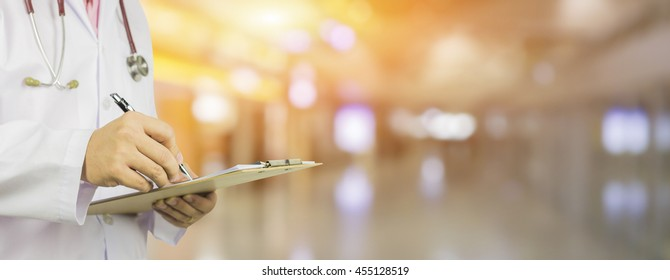 Male Doctor with files and stethoscope on hospital corridor holding clipboard and writing prescription,Doctor,Medical Exam Healthcare and medical concept,test results, registration,banner blackground