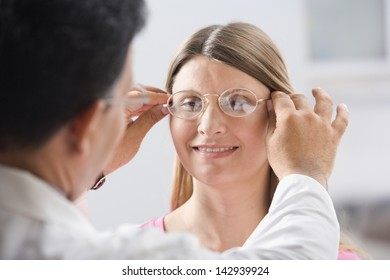 Male doctor fitting glasses on woman