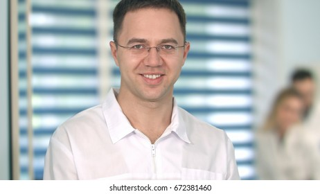 Male doctor in glasses smiling at camera while medical staff working on the background