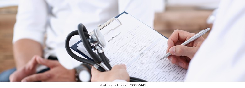 Male doctor hand hold silver pen filling patient history list at clipboard pad. Physical, exam, er, disease prevention, ward round, visit check, 911, prescribe remedy, healthy lifestyle concept