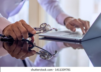 Male doctor hand holding stethoscope, working and typing on laptop computer keyboard on the desk at clinic or hospital.Teleconference,telehealth, online medical,medic tech,emr,ehr,telemedicine concept