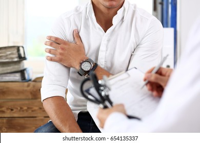 Male doctor hold silver pen filling patient history list at clipboard pad. Physical, exam, er, trauma pain, disease prevention, ward round, 911, prescribe remedy, healthy lifestyle concept