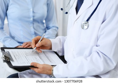 Male doctor holding application form while consulting female patient in hospital. Medicine and healthcare concept