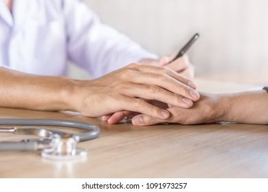 male doctor holding hand and comforting patient in a hospital with blur stethoscope in foreground on desk