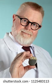 Male Doctor holding Pacemaker in front of camera with blue background