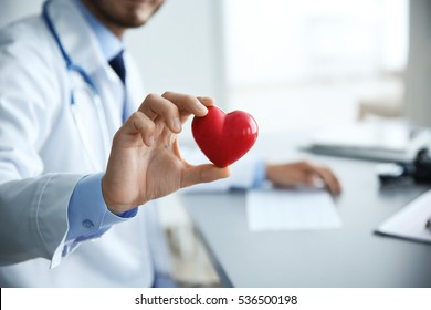 Male doctor holding red heart in clinic office
