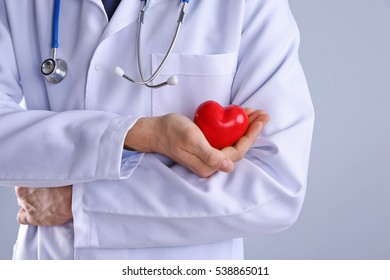 Male doctor holding red heart on light background