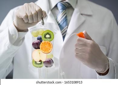 Male Doctor Holding Saline Bag With Fruit Slices Inside In Hospital