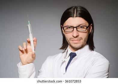 Male doctor holding syringe against gray