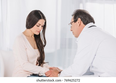 male doctor holding upset female patient hands