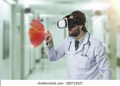 Male doctor at a hospital , using a Virtual Reality Glasses, looking at a virtual heart.