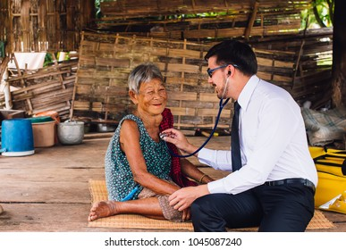 Male Doctor listening heart beat and breathing of Elderly Woman with Stethoscope with First Aid Medical Box.Community Health and Development Hospital In Remote Areas Development Fund Concept.