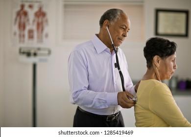 Männlicher Arzt hörte dem Herzschlag eines reifen weiblichen Patienten in seinem Büro zu.