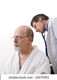 Male doctor listening to a senior male's breathing with a stethoscope, isolated on white.