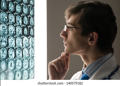 male doctor looking at the x-ray image attached to the glowing screen