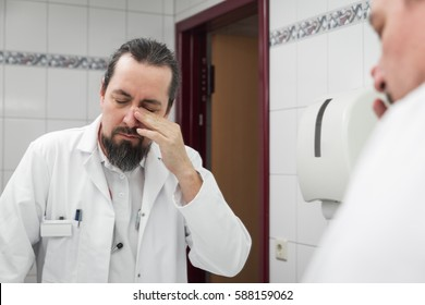 male doctor looks tired into the mirror in a bathroom