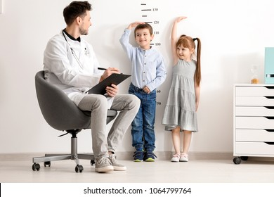 Male doctor measuring height of little children in clinic