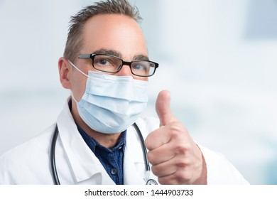 male doctor with medical face mask shows thumb up