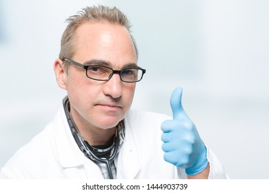 male doctor with medical gloves shows thumb up