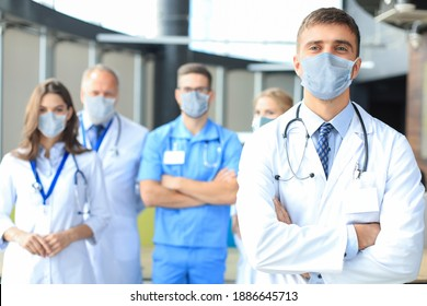 Male doctor in medical mask with group of happy successful colleagues also in preventive masks. - Shutterstock ID 1886645713