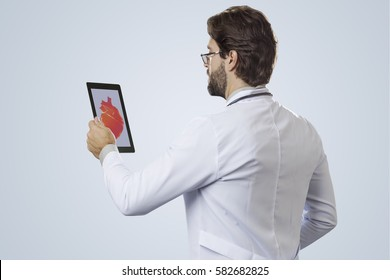 Male doctor on a gray background, looking at a tablet.