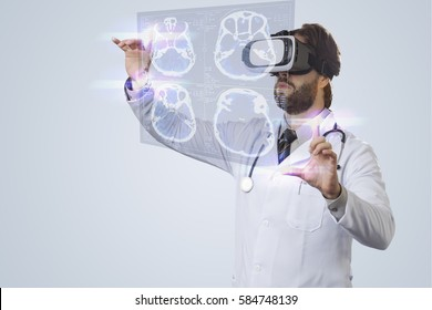 Male doctor on a gray background, using a Virtual Reality Glasses, looking at a virtual Screen.