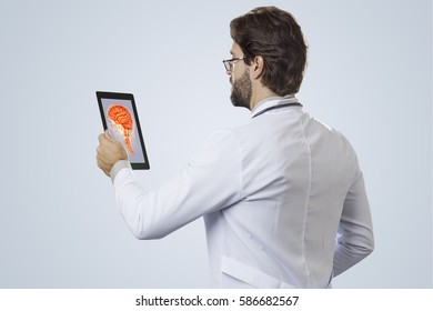 Male doctor on a gray background, looking at a brain image on a tablet.