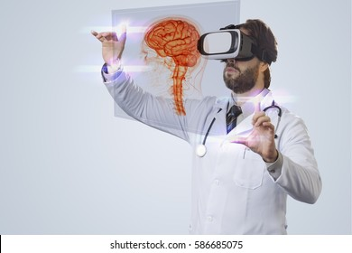 Male doctor on a gray background, using a Virtual Reality Glasses, looking at a virtual brain.