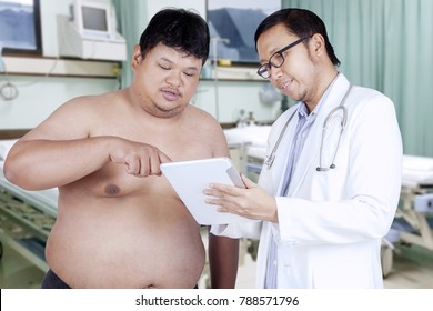 Male doctor and overweight patient discussing an examination result on the digital tablet in hospital