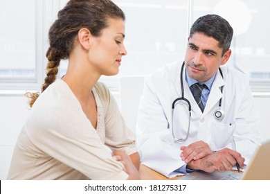 Male doctor and patient in discussion at desk in medical office