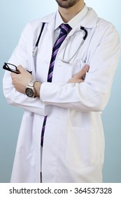 Male doctor is posing with confidence in front of blue vignette background.