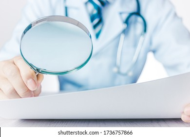 Male doctor reading materials with a magnifying glass
