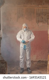 A male doctor and scientist wearing a full white protective suit face mask and gloves to inspect an infected destroyed house during a sars corona virus world pandemic