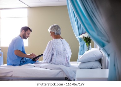 Male doctor showing medical report to female senior patient on a digital tablet in the hospital