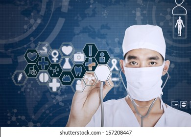 Male doctor with stethoscope and blue virtual screen