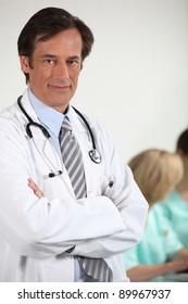 Male doctor stood with arms folded colleagues in background